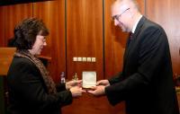 Doc. PhDr. Mikuláš Bek, Ph.D., prorektor MU pro strategii a vnější vztahy předává Zlatou medaili Masarykovy univerzity paní vládní radové Christine Dollingerové